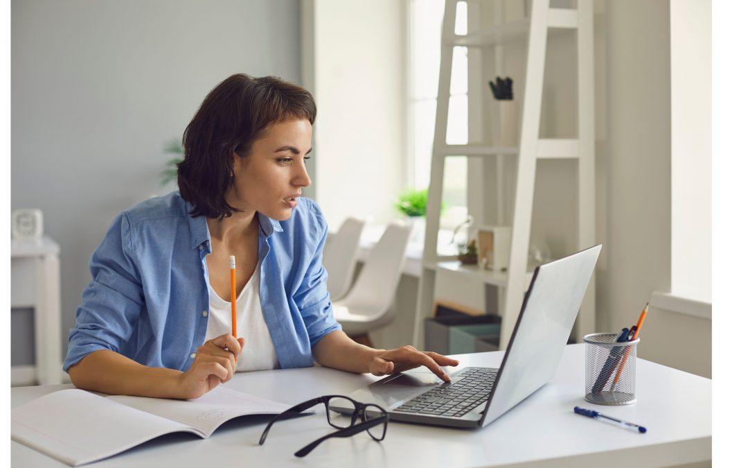 Na imagem, uma moça utilizando um computador em sua casa